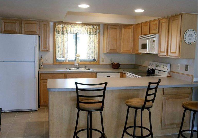 Рабочая зона на этой кухне значительно увеличилась и приобрела П-образный вид благодаря совмещенной барной стойке