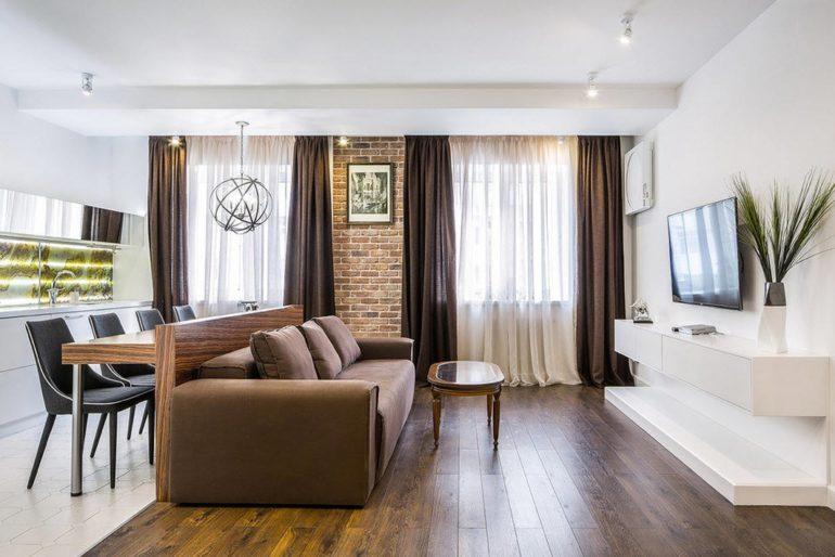 На этой кухне диван и барная стойка  разделяют пространство на зону готовки и зону для отдыха