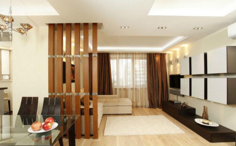 Эта легкая перегородка из вертикальных деревянных реек визуально поднимает многоуровневый потолок