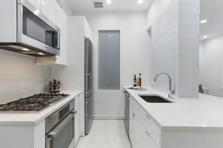 Белый цвет отделки скроет несовершенство архитектуры, а светлый гарнитур сделает кухню визуально шире