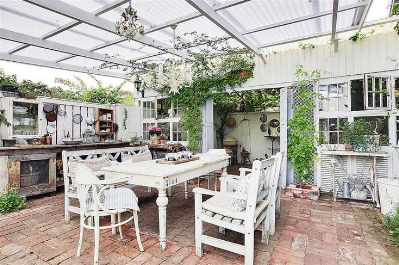 Пристраиваемая к дому летняя кухня может быть полностью застекленной или в виде открытой площадки с навесом