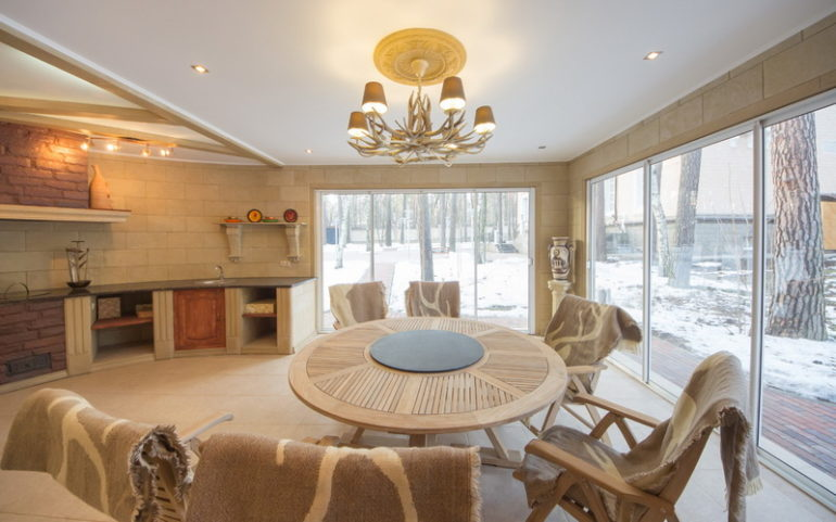 Закрытая летняя кухня – застекленная веранда, оснащенная всем необходимым оборудованием и обставленная мебелью