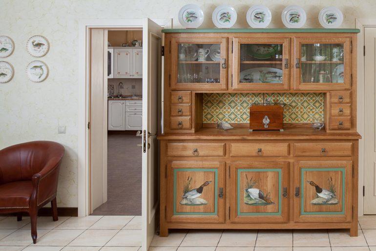 Покрытый лаком кухонный буфет с элементами росписи на филенках