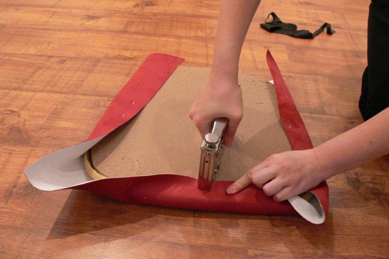 Огибаем сиденье материалом и фиксируем степлером